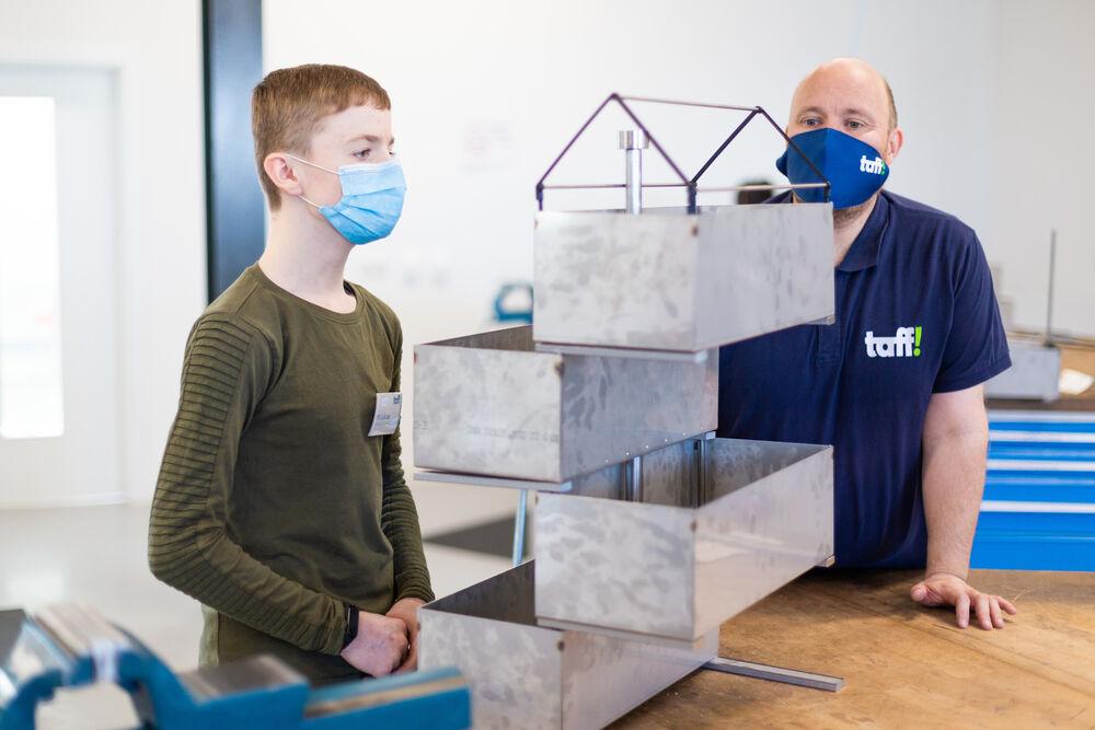Ausbildungsleiter Markus Tönjes schaut bei Pit noch mal genauer hin. Selbst die Dachkonstruktion aus dem 3D-Drucker passt perfekt in den Kasten. (Michael Galian)
